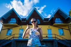 Glückliche junge Geschäftsfrau in der Sonnenbrille kaufte ein großes Haus für ihre Familie stockbilder