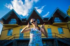 Glückliche junge Geschäftsfrau in der Sonnenbrille kaufte ein großes Haus für ihre Familie lizenzfreie stockbilder