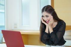 Glückliche junge Geschäftsfrau, die den Laptopschirm überrascht betrachtet Stockfoto