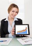 Geschäftsfrau, die Diagramme auf Digital-Tablette darstellt Lizenzfreies Stockbild