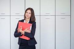 Glückliche junge Geschäftsfrau, die eine rote Mappe und ein Lächeln hält Lizenzfreie Stockbilder
