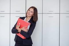 Glückliche junge Geschäftsfrau, die eine rote Mappe und ein Lächeln hält Stockfoto