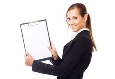 Glückliche junge Geschäftsfrau, die leeres Papier auf Klemmbrett anhält Lizenzfreies Stockbild