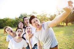 Glückliche junge Gruppe, die selfie im Park nimmt Stockfotos