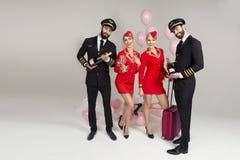 Glückliche junge Gruppe Piloten und Stewardesse lizenzfreie stockfotos