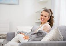 Glückliche junge Hausfrau, die im Wohnzimmer sitzt stockbild