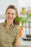 Glückliche junge Hausfrau, die Karotte in der Küche hält Stockbilder
