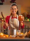 Glückliche junge Hausfrau, die Orangenmarmelade in der Küche zeigt lizenzfreie stockfotos
