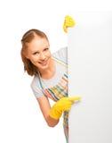 Glückliche junge Hausfrau im Handschuh mit weißem leerem Anschlagtafel isolat Lizenzfreies Stockfoto