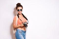 Glückliche junge Hippie-Frau in den Gläsern hält Retro- Fotokamera stockfoto