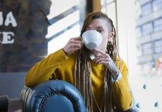 Glückliche junge Hippie-Frau, die in der Kaffeestube sitzt stockfoto