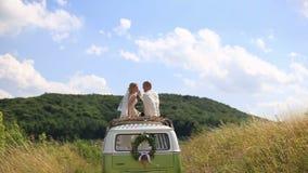 Glückliche junge Jungvermählten Braut und Bräutigam auf die Oberseite des rerto Hochzeitsbusses auf dem sonnigen Sommergebiet Zar stock video footage