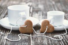 Glückliche junge küssende und celabrating Paare Herz-förmige Kekse und Schalen Stockfotografie