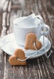 Glückliche junge küssende und celabrating Paare Herz-förmige Kekse und Schalen Stockbilder
