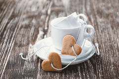 Glückliche junge küssende und celabrating Paare Herz-förmige Kekse und Schalen Lizenzfreies Stockfoto