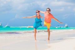 Glückliche junge kaukasische Paare in der Sonnenbrille, die ihre Zeit auf Strand genießt Stockfotografie