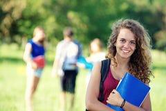 Glückliche junge Kursteilnehmer des Portraits im Park Lizenzfreie Stockfotografie