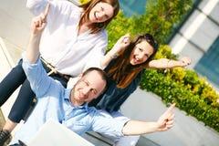 Glückliche junge Kursteilnehmer mit den Händen oben Stockfoto