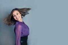 Glückliche junge lächelnde Frau auf grauem backgroung Lizenzfreie Stockbilder