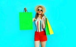 Glückliche junge lächelnde Frau des Porträts, die Einkaufstaschen im bunten T-Shirt, Sommerrundenhut auf blauer Wand hält lizenzfreie stockfotos