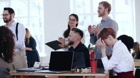 Glückliche junge lächelnde verschiedene Geschäftsleute Applaus zum Sprecher am Bürotisch nach Konferenzseminartraining stock footage