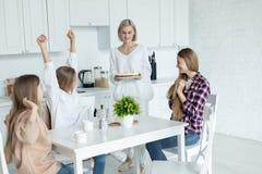 Gl?ckliche junge lesbische Familie, die zu Hause Geburtstag ihrer Tochter in der K?che feiert stockfotos