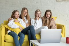Gl?ckliche junge lesbische Paare mit T?chtern in der zuf?lligen Kleidung, die zusammen zu Hause auf gelbem Sofa sitzt stockfotografie