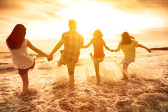 glückliche junge Leute, die auf dem Strand spielen Lizenzfreies Stockfoto
