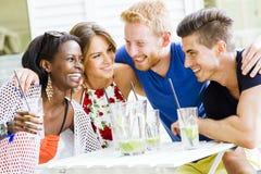 Glückliche junge Leute, die ein Wesen glücklich an einem Tisch lachen Lizenzfreies Stockfoto