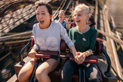 Glückliche junge Leute, die eine Achterbahn reiten Lizenzfreies Stockfoto