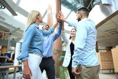 Glückliche junge Leute, die im Büro stehen und ihren Kollegen Hoch fünf geben stockfotos