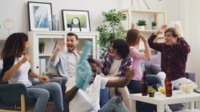 Glückliche junge Leute, die im Fernsehen das Sportspiel zu Hause das Spaßumarmen habend genießen stock footage