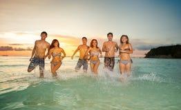 Glückliche junge Leute, die im Meer spielen Stockfotografie