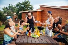 Glückliche junge Leute, die Spaß auf Grillpartei lachen und haben lizenzfreie stockfotos