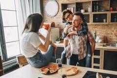 Glückliche junge Leute, die Spaß zusammen, lächelnd haben und essen die Pizza stockfotos