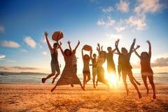 Glückliche junge Leute, die am Strand auf schönem Sonnenuntergang springen stockfotos