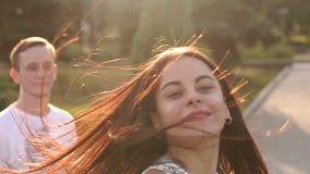 Glückliche junge liebevolle Paare, die einen langsamen Walzer bei Sonnenuntergang im Park tanzen stock footage
