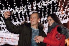 Glückliche junge liebevolle Paare, die selfie in der Stadt nachts machen stockfoto