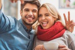Glückliche junge Liebhaber, die Foto auf Smartphone machen Stockbilder