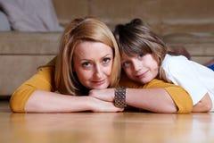 Glückliche junge Mamma, die auf Fußboden mit ihrem Sohn liegt Stockfotografie