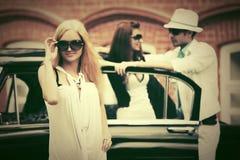 Glückliche junge Modefrau in der Sonnenbrille nahe bei Retro- Auto Lizenzfreies Stockbild