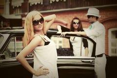 Glückliche junge Modefrau in der Sonnenbrille nahe bei Retro- Auto Stockfoto