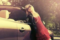 Glückliche junge Modefrau, die auf ihrem konvertierbaren Auto sich lehnt Stockbilder