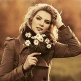 Glückliche junge Modefrau im beige Mantelgehen im Freien Stockbild