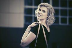 Glückliche junge Modefrau im schwarzen Kleid gehend in Stadtstraße Lizenzfreie Stockfotografie