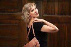 Glückliche junge Modefrau im schwarzen Kleid gehend in Stadtstraße Stockfotografie