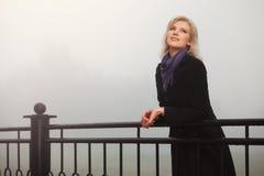Glückliche junge Modefrau im schwarzen Mantel in einem Nebel im Freien Stockfotos