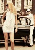 Glückliche junge Modefrau im weißen Kleid nahe bei Weinleseauto Lizenzfreie Stockfotografie