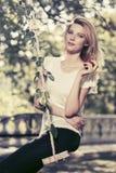 Glückliche junge Modefrau mit Apfel auf Schwingen im Stadtpark Stockfotografie