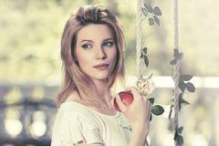 Glückliche junge Modefrau mit Apfel im Stadtpark Lizenzfreies Stockbild